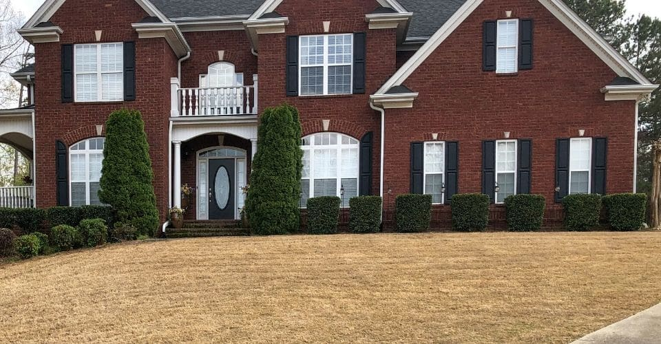 2-story residential brick home with a manicured lawn and landscape after a yard cleanup service.