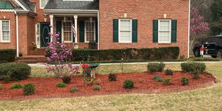 Large red mulch landscape bed with a bird bath shrubs and roses in front of red brick house with green shutters.