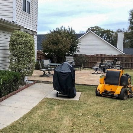 Side view of backyard with a grill and yellow riding mower around patio.