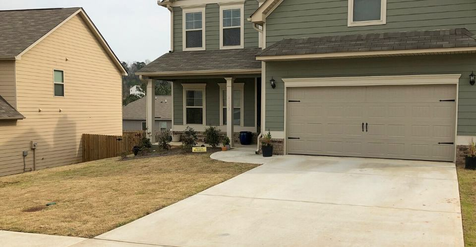 Freshly cleaned lawn and driveway in front of a green siding house.
